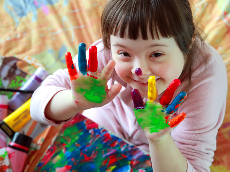 Young smiling girl finger-painting